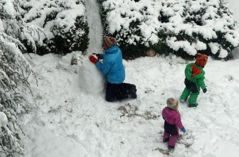 Making snowmen in the back yard.